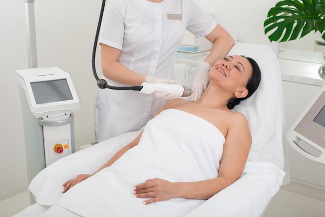 Serene lady taking procedure in wellness center